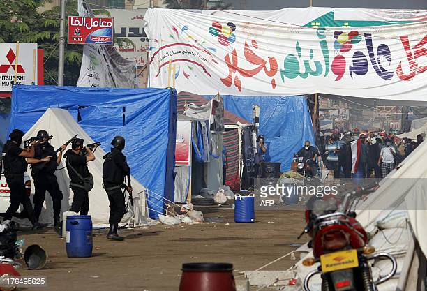 Egyptian riot policemen point their guns towards protesters as security forces moved in to disperse supporters of Egypt's deposed president Mohamed...