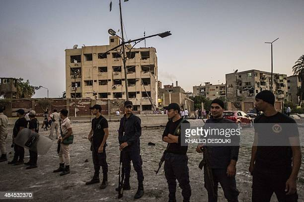 Egyptian riot policemen stand in front of the damaged national security building in northern Cairo's district of Shubra on August 20 2015 A car bomb...