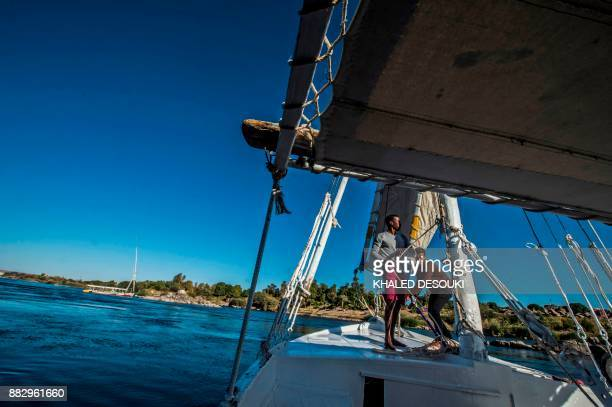 Egyptian sailors pull the ropes on the sail of a felucca as they cruise down the Nile in the city of Aswan some 920 kilometres south of the capital...
