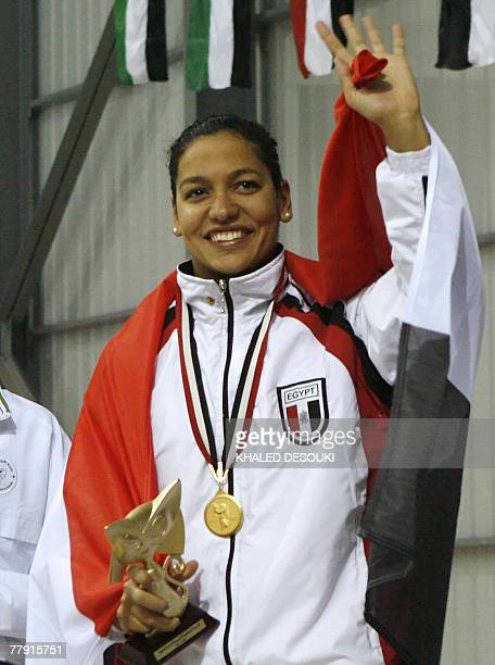 Egyptian Salma Zenhum poses on the podium with her national flag after winning the gold medal in the 50m Breast stroke during the 11th Pan Arab Games...