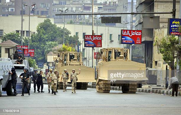 Egyptian security forces backed by bulldozers move in on August 14, 2013 on one of two huge protest camps set up in Cairo's Al-Nahda square by...