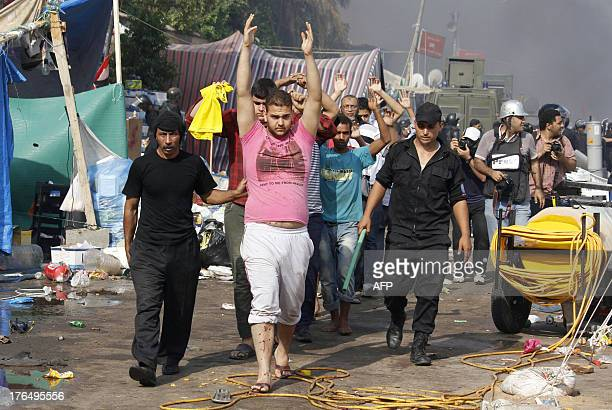 Egyptian security forces escort detained supporters of Egypt's ousted president Mohamed Morsi during an operation to dismantle a huge pro-Islamists...