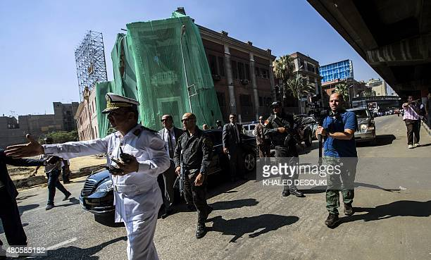 Egyptian security forces escort the convoy of Italian Foreign Minister Paolo Gentiloni as it drives past the bombed Italian consulate in Cairo on...