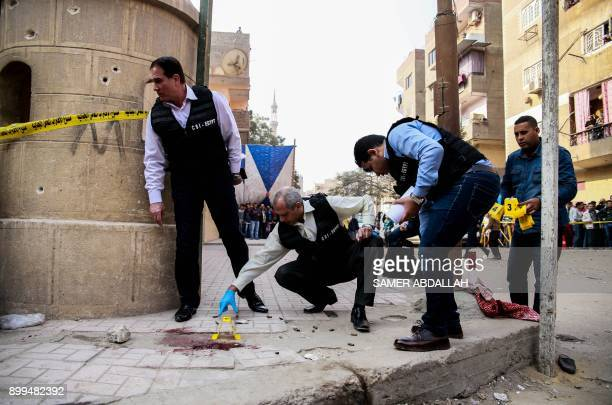 TOPSHOT Egyptian security members and forensic police inspect the site of a gun attack outside a church south of the capital Cairo on December 29...