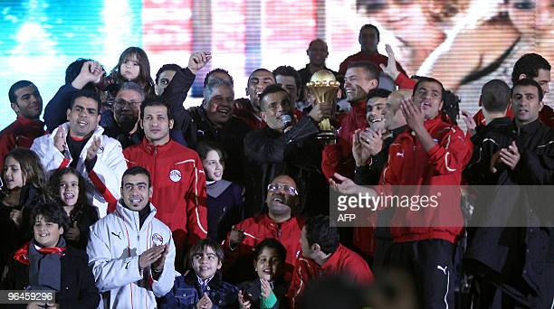Egyptian singer Amr Diab holds the trophy of the African Cup of Nations as he is joined by players of the Egyptian national football team recently...