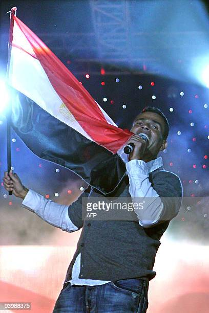 Egyptian singer Amr Diab waves his national flag as he performs during a concert at Future University in Cairo late on December 4 2009 AFP PHOTO/STR