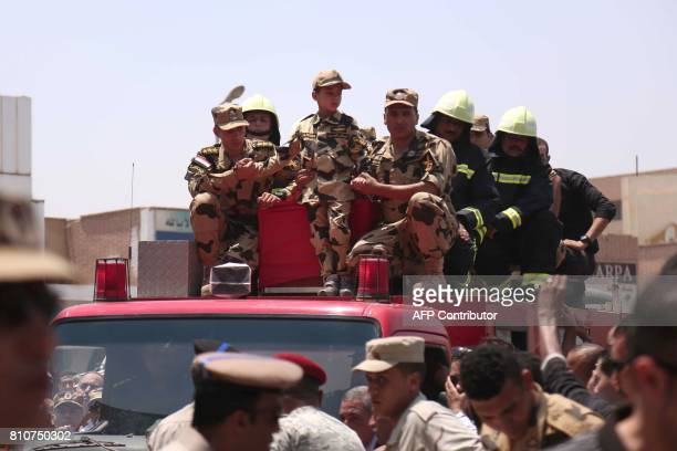 Egyptian soldiers and a boy dressed in a military outfit stand on a vehicle carrying the coffins of soldiers who were killed a day earlier in the...