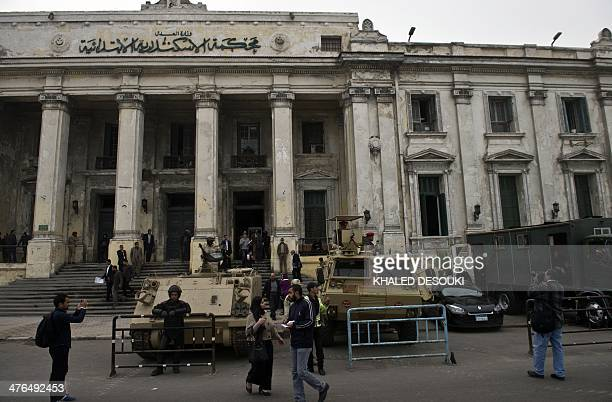 Egyptian soldiers and police stand guard with armoured personnel carriers outside the criminal court in Egypt's Mediterranean city of Alexandria on...