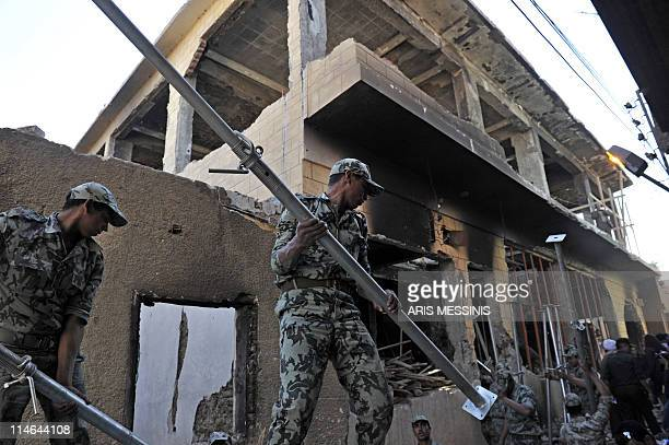 Egyptian soldiers carry construction material to start rebuilding the church that was set ablaze last week sparking deadly clashes between Muslims...