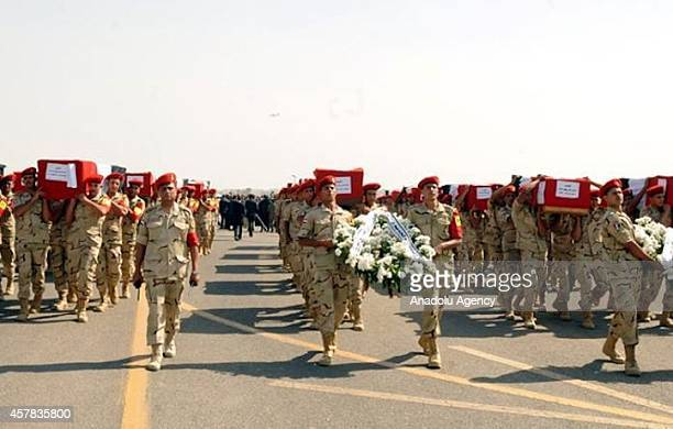 Egyptian soldiers carry the coffins of the people killed in a bombing attack of northern Sinai during the funeral ceremony in Cairo Egypt on October...
