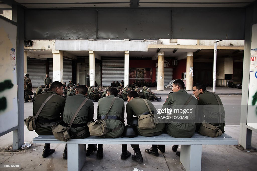 Egyptian soldiers deployed in the area of the Presidential Palace in Cairo sit at a bus stop on December 11, 2012