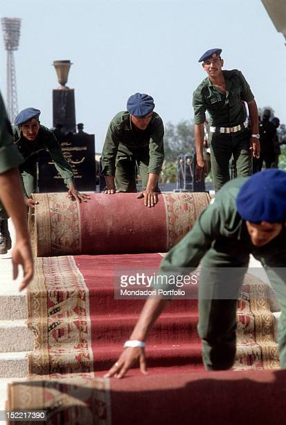 Egyptian soldiers roll up the red carpet at the end of the President Sadat funerals on the background appears the grave with the epigraph Medinet Nars