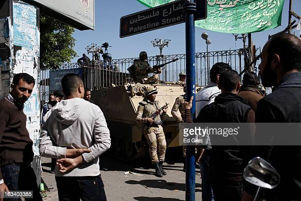 Egyptian soldiers stand guard near the Suez Canal as Port Said residents look on after the announcement of the final verdict in the case of the Port...
