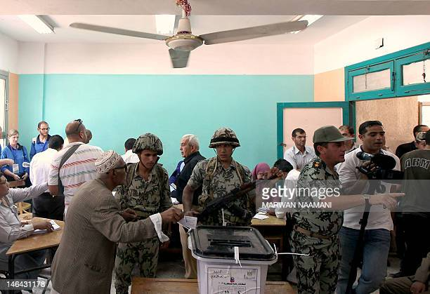 Egyptian soldiers stand guard next to a ballot box as an elderly man casts his vote in the second round of the historical presidential election at a...