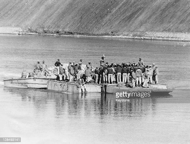 Egyptian soldiers transport food across the Suez Canal to the members of their Third Army, from the Egyptian side of Suez, October 1973. This is...