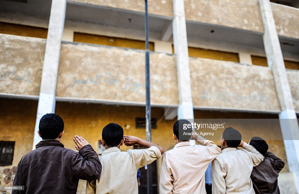 Egyptian students are seen at the garden of a primary school, where nearly 2 thousand students get education, during the Egyptian national anthem performance in Baragil neighborhood of Giza, Egypt on October 30, 2014. Head master of the school complains about the crowded classroom sizes, reaching up to 70, lack of the desks and other impossibilities. Formal education, at every level, is provided freely at state schools in Egypt. Downswing due to the ongoing 4-year unrest, Egypt tries to overcome many difficulties and uncertainties.