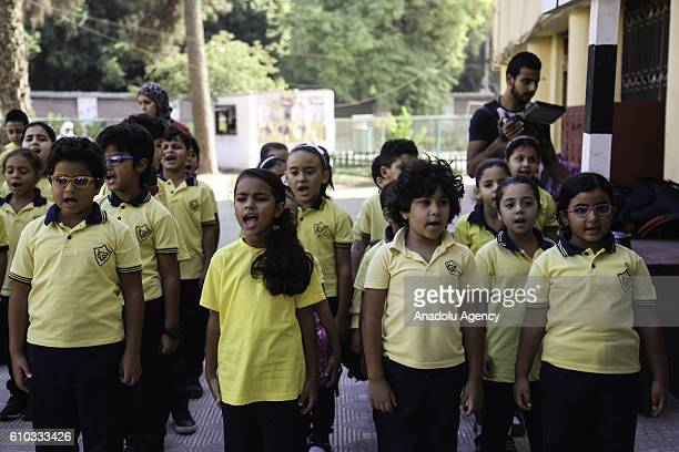 Egyptian students sing their national anthem as Egyptian Education Minister AlHilali Al Sherbini arrives to inspect the regulations of the new school...