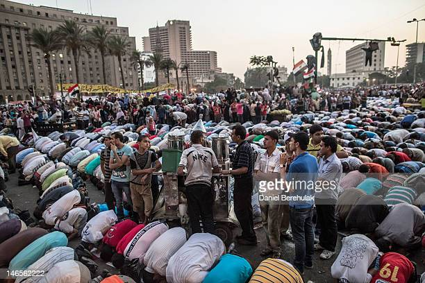 Egyptian supporters of the Muslim Brotherhood pray as thousands gather to celebrate a premature victory for their presidential candidate Mohamed...
