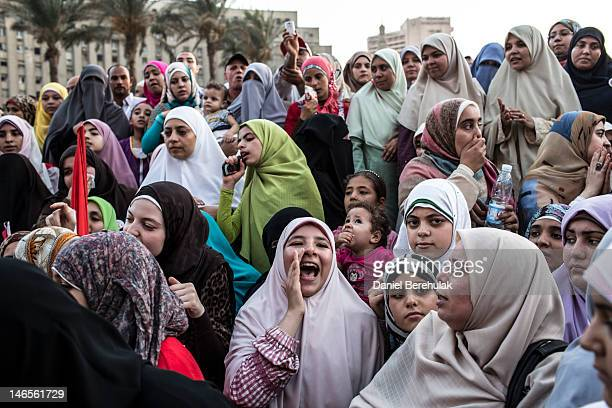 Egyptian supporters of the Muslim Brotherhood, react to speeches at a gathering to celebrate a premature victory for their presidential candidate...