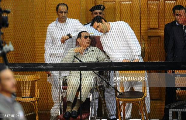 Egyptian toppled president Hosni Mubarak and his two sons Alaa and Gamal stand behind bars during their trial at the Police Academy on September 14,...