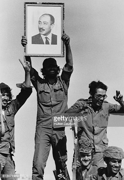 Egyptian troops shout with joy as a soldier holds up a picture of President Anwar elSadat during the Yom Kippur War against Israel