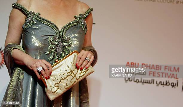 Egyptian TV presenter Hala Serhan poses with a designer handbag bearing Arabic calligraphy at the opening ceremony of the Abu Dhabi Interntional Film...