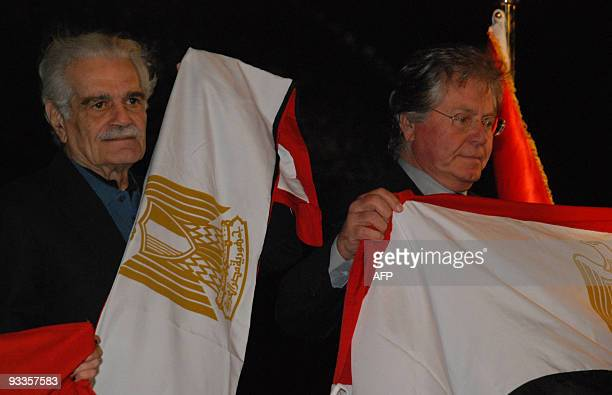 Egyptian veteran film stars Omar Sharif and Hussein Fahmi hold national flags during an event at the Giza Pyramids plateau south of Cairo held on...