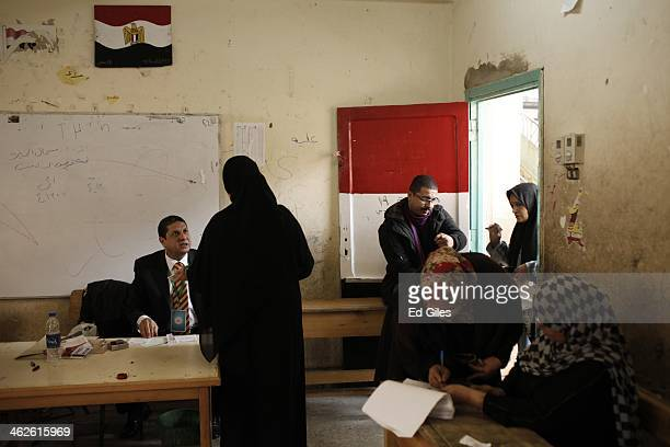 Egyptian voters stand in at voting room art a polling booth in the district of Imbaba on January 14 2014 in Cairo Egypt Some clashes between...