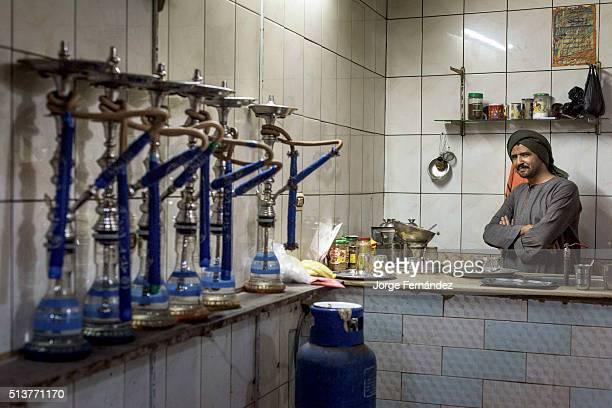 Egyptian waiter inside his small shisha bar, where people comes to smoke water pipes and play games.