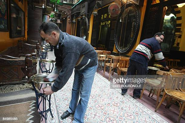 Egyptian waiters clean tables as they open the popular ElFishawi coffee shop in the tourist bazaar close to the AlHussein mosque in Cairo early on...