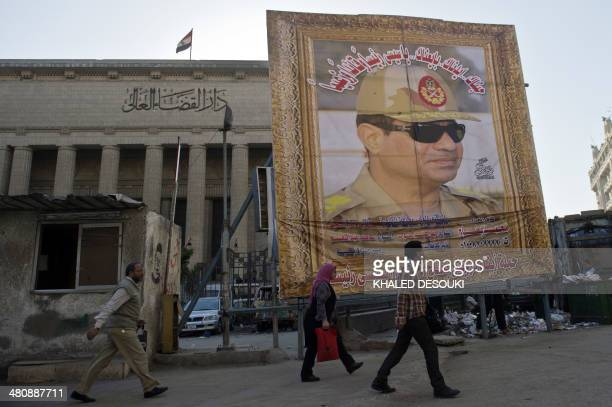 Egyptian walk past a huge poster of Egypt's former Defence Minister and armed forces chief General Abdul Fatah AlSisi outside the High Court in...