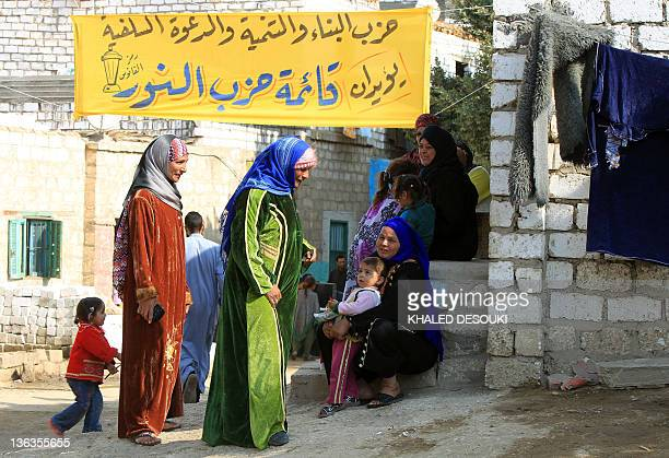 Egyptian women and children gather under an electoral campaign banner near a polling station in Minya, some 350 kms south of Cairo, during the third...