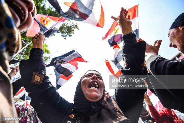 Egyptian women chant slogans and wave together national flags outside polling stations in a referendum on constitutional amendments at a school in...