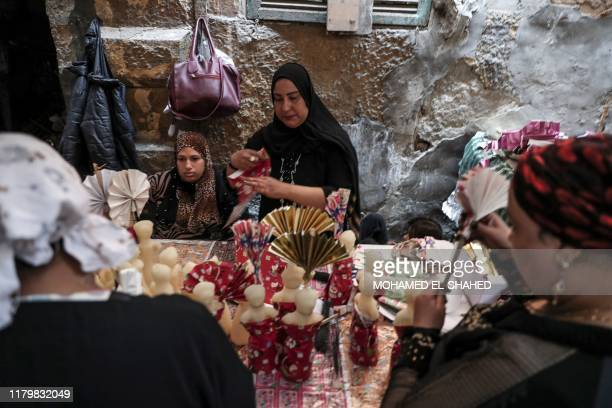 Egyptian women decorate traditional sugar statuettes in the capital Cairo on November 2 ahead of celebrations of the Muslim Prophet Mohammed's...