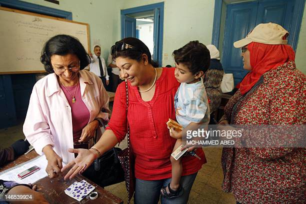 Egyptian women dip their fingers in ink after casting votes at a polling station in Cairo on June 16 2012 in a divisive presidential runoff pitting...