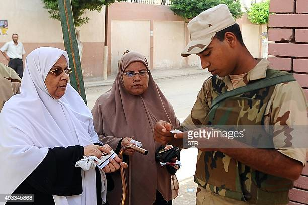 Egyptian women display their ID for a member of the army ahead of casting her vote at a polling station in Egypt's northern coastal city of...