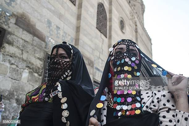 Egyptian women dressed in their country's traditional clothing walk at alMezz street during a celebration ahead of the Muslim holy month of Ramadan...