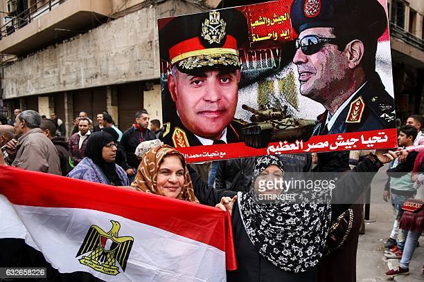 Egyptian women hold their national flag and a poster bearing portraits of President Abdel Fattah alSisi and Defense Minister Sedki Sobhi as they...