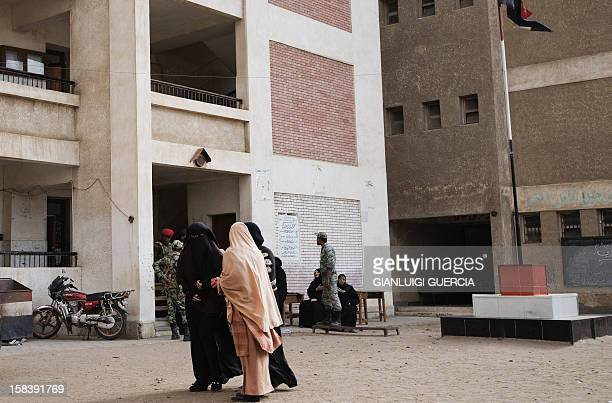 Egyptian women leave a polling station after casting their votes in a referendum on a new constitution in President Mohamed Morsi's hometown Adwa in...