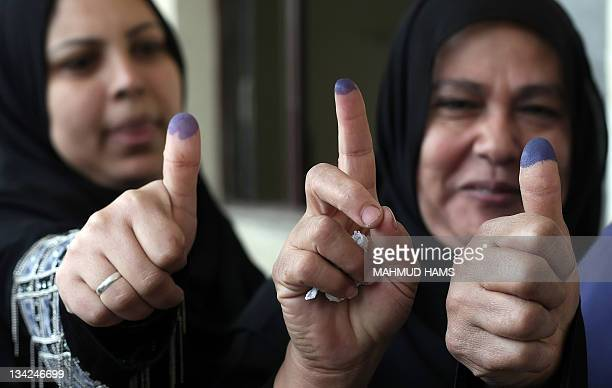 Egyptian women show their inkstained fingers at a parliamentary polling station in Cairo on November 29 2011 Egypt hailed the start of its first...