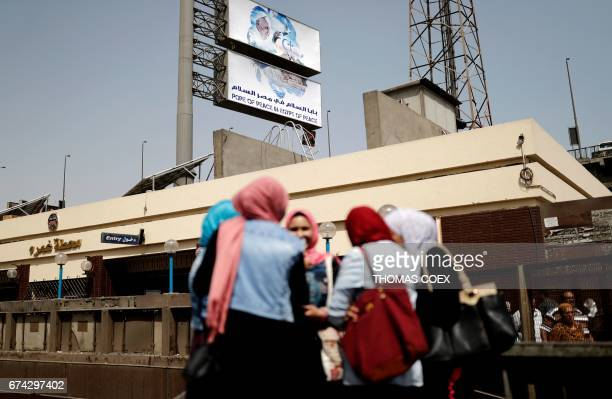 Egyptian women stand at a Metro station in the capital Cairo with a billboard seen in the background depicting Pope Francis a few hours before his...