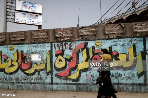 Egyptian women walk down a street past graffitied advertisements in the capital Cairo with a billboard seen in the background depicting Pope Francis...