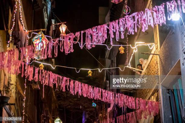 Egyptian women watch from their balcony as youths decorate their residential street in preparation for the Muslim holy month of Ramadan in Cairo's...