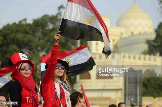 Egyptian women wave national flags during the celebration marking the 40th anniversary of the 1973 victory over Israel around the Ittihadiya...