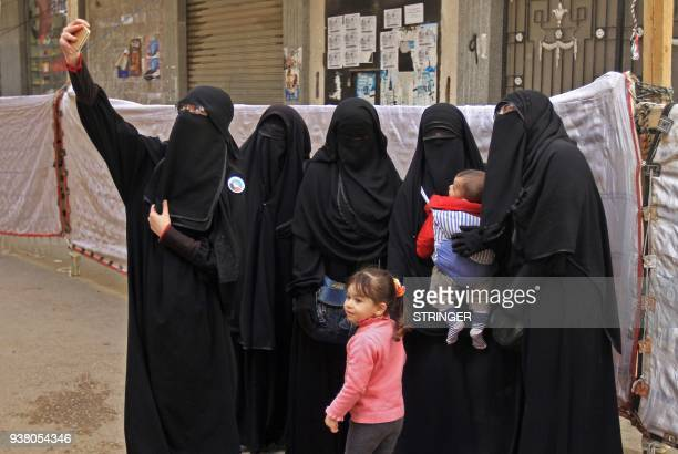 Egyptian women wearing niqab pose for a selfie photograph with a cell phone outside a polling station in alMontazah district of Egypt's second city...