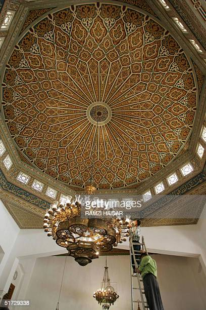Egyptian workers clean 11 November 2004 the glass diffusers of a chandelier hanging from the dome of the King Faisal Mosque near Cairo international...