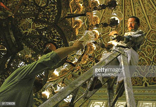 Egyptian workers clean the glass diffusers of a chandelier in the King Faisal Mosque close to the international airport in Cairo 11 November 2004,...