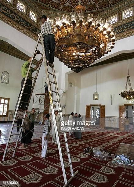 Egyptian workers clean the glass diffusers of a chandelier in the King Faisal Mosque close to the international airport in Cairo 11 November 2004...