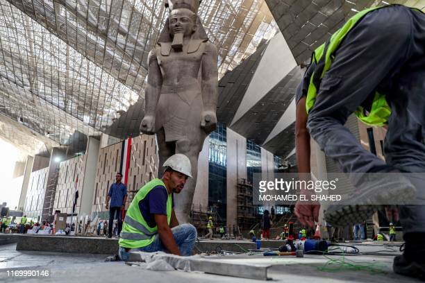 Egyptian workers continue construction work near the colossus of ancient Egyptian Pharaoh Ramses II, at its permanent display spot in the newly-built...