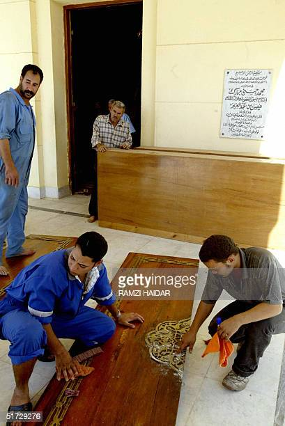 Egyptian workers polish a door of the King Faisal Mosque close to the international airport in Cairo 11 November 2004, where the body of Palestinian...